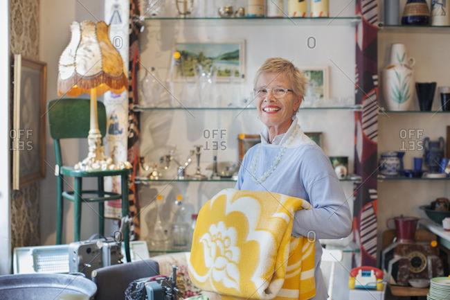 Portrait of mature woman folding yellow blanket in vintage shop