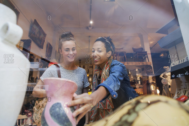 Young woman shopping for pink vase in vintage shop