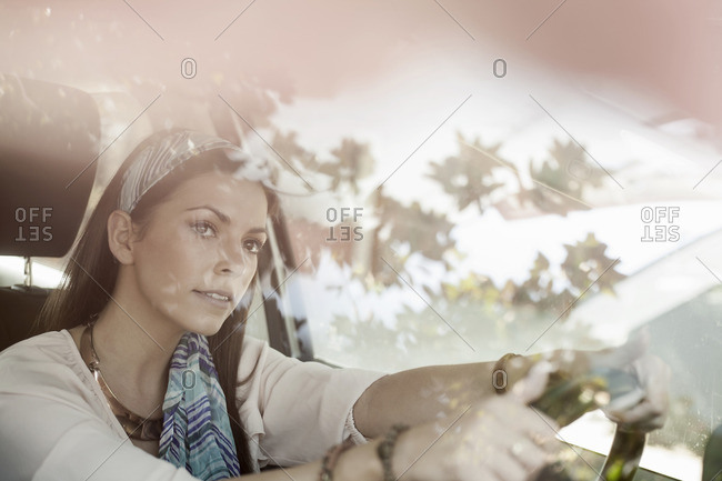 Young woman driving, looking through windscreen