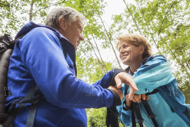 Couple in forest, face to face, smiling, low angle view