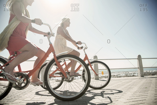 Young women cycling on seafront, Cape Town, South Africa