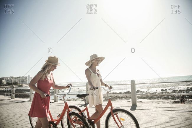 Young women walking with bicycle on seafront, Cape Town, South Africa