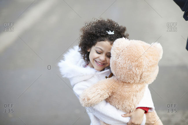 High angle view of girl, eyes closed hugging soft toy