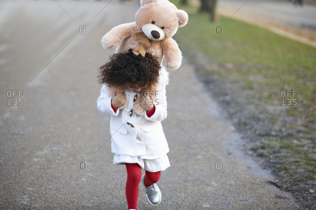 Front view of girl carrying soft toy on shoulders looking down