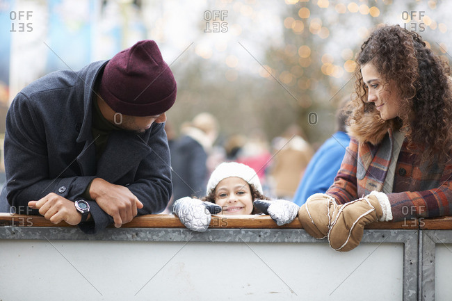 Girl with parents peeking over barrier, looking at camera smiling