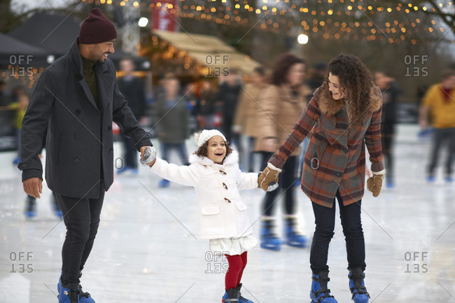 Girl holding parents hands ice skating, smiling