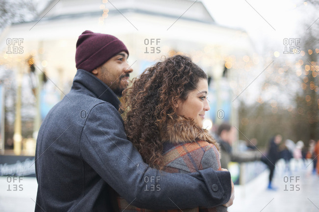 Rear view mid adult man wearing knit hat with arm around young woman, looking away smiling