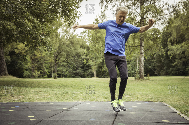 Full length front view of senior man in park jumping in mid air