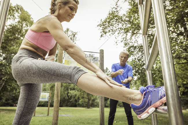 Side view of mature woman leg raised on playground equipment bending forward stretching