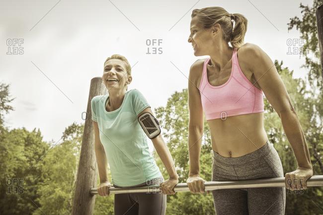 Mature women in park doing push ups on metal bar smiling