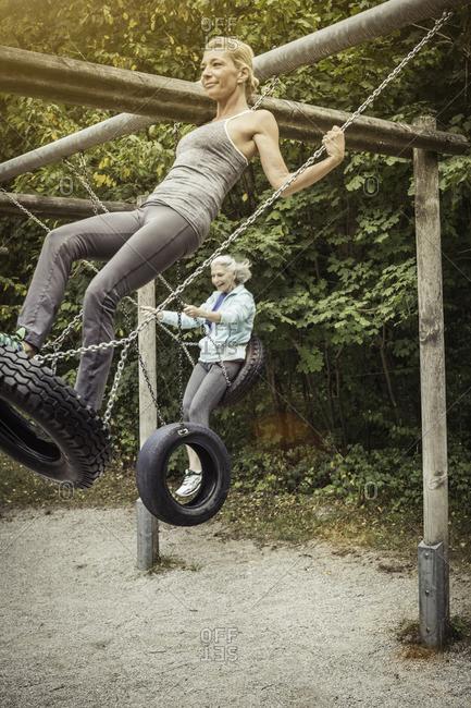 Side view of women standing on tire swings, swinging
