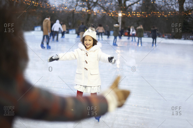 Girl on ice rink, arms open skating to mother smiling