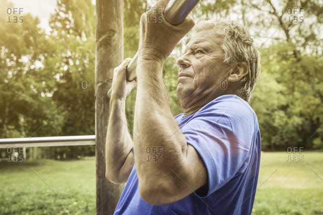 Side view of senior man in park doing pull up on metal bar