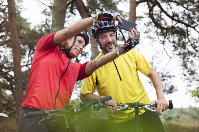 Happy mountain biking couple taking smartphone selfie in forest