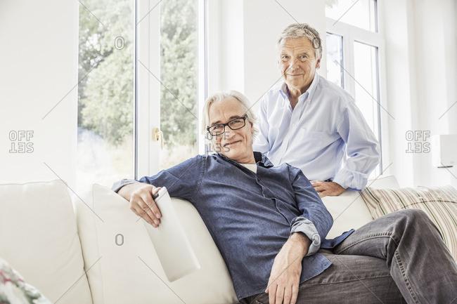 Two men relaxing on sofa