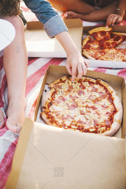 Cropped view of friends sharing a pizza