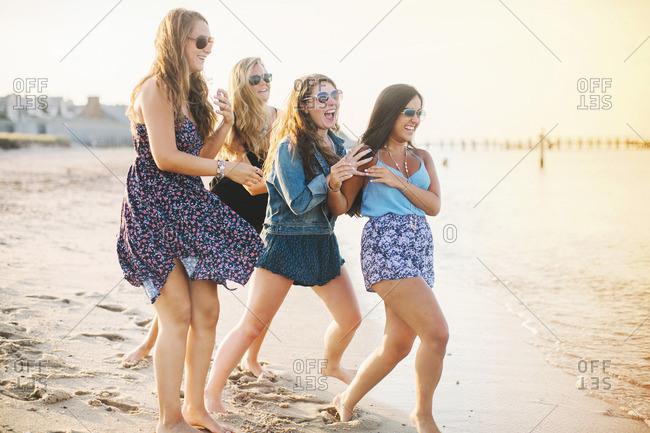 Women wearing sunglasses on beach fooling around laughing