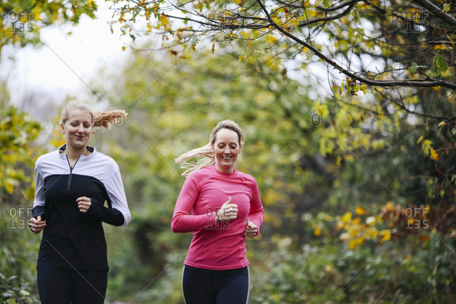 Teenage girl and woman running in park