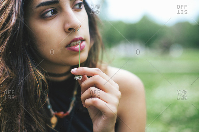 Woman with nose ring chewing grass looking away