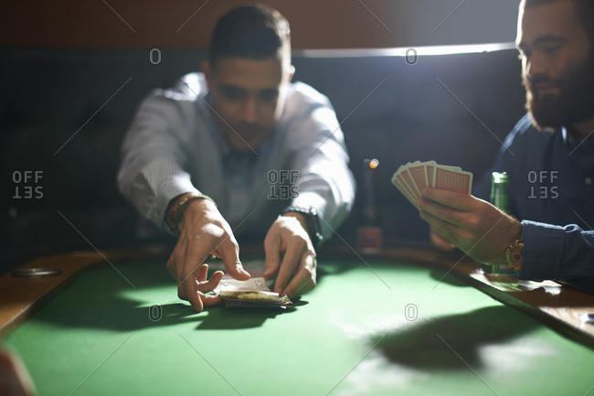 Man picking up card game winnings at pub card table