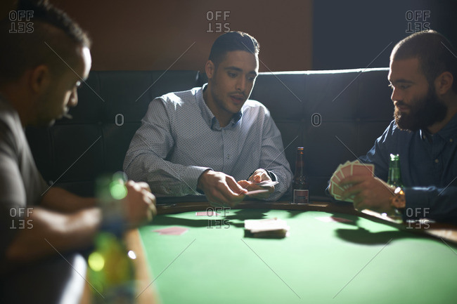 Male friends dealing playing card for game at pub card table