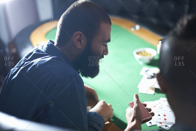 Over the shoulder view of men playing card game at pub card table