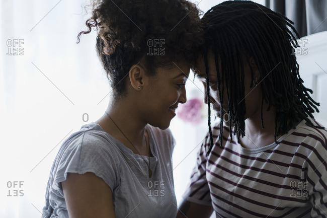 Lesbian couple relaxing in bedroom, face to face
