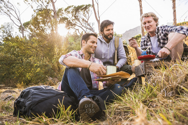 Three men frying breakfast on camping stove in forest, Deer Park, Cape Town, South Africa