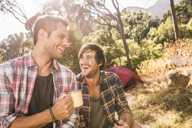 Two male campers chatting over coffee in forest, Deer Park, Cape Town, South Africa