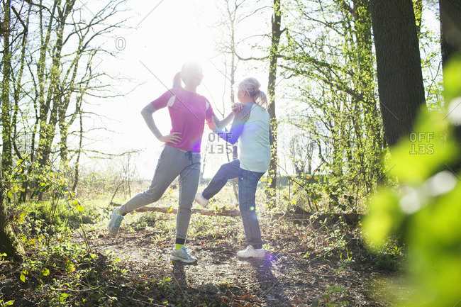 Women in forest face to face legs raised stretching
