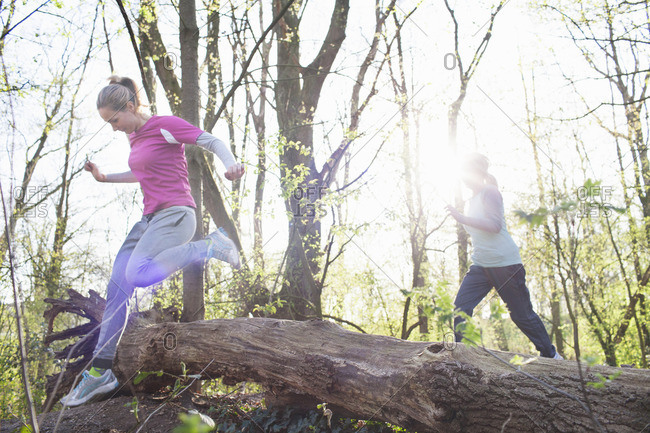 Women in forest jumping over fallen tree