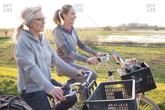 Side view of women cycling by marshland smiling