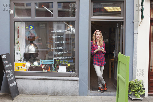 Woman standing in shop doorway holding coffee cup looking at camera