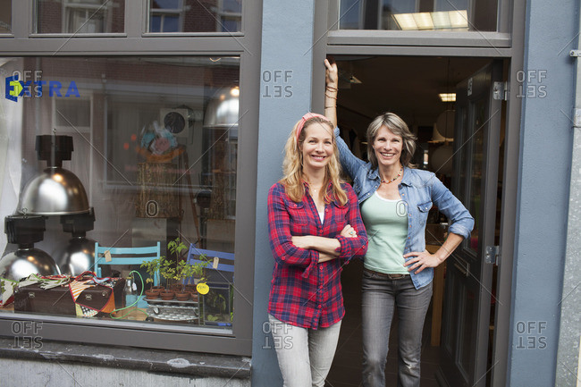 Women standing in shop doorway looking at camera smiling