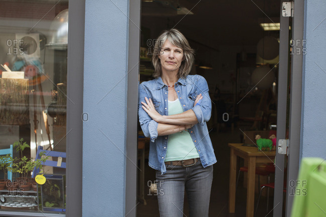Woman in shop doorway, arms crossed looking at camera