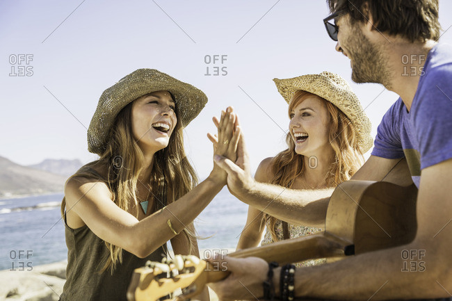 Mid adult friends playing guitar and high fiving at coast, Cape Town, South Africa