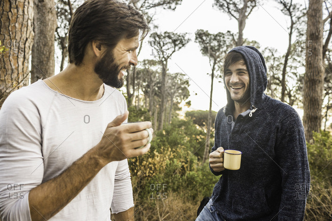 Two men drinking coffee and chatting in forest, Deer Park, Cape Town, South Africa