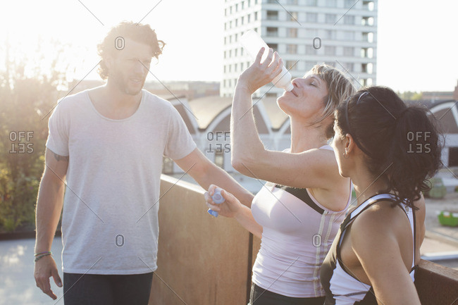 Two women and man training, drinking water on urban footbridge