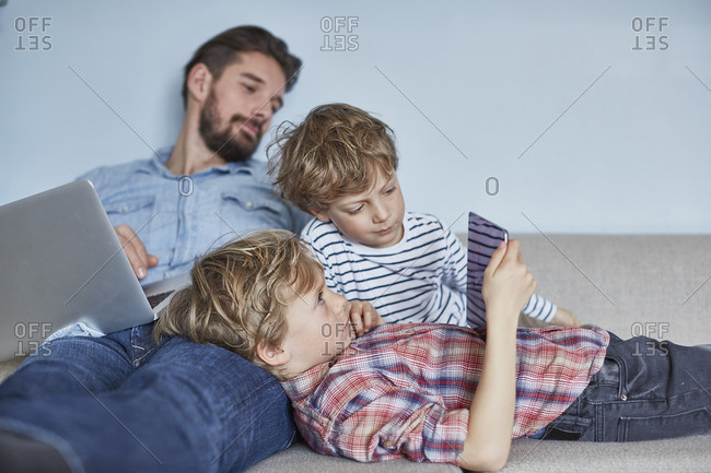 Boys lying on sofa with father using technology