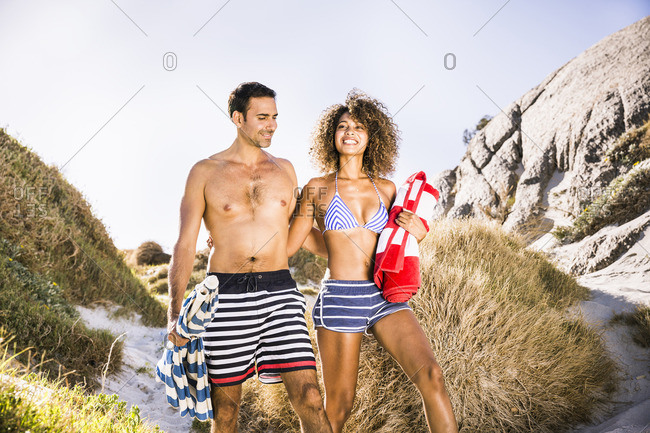 Couple walking down sand dune carrying beach towel and umbrella, Cape Town, South Africa