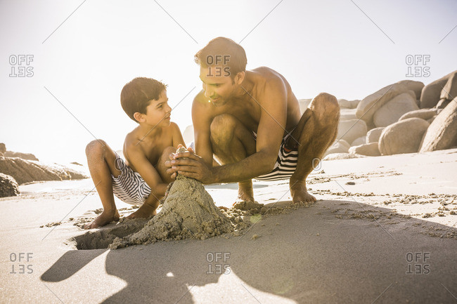 Boy and father making sandcastle on beach, Cape Town, South Africa
