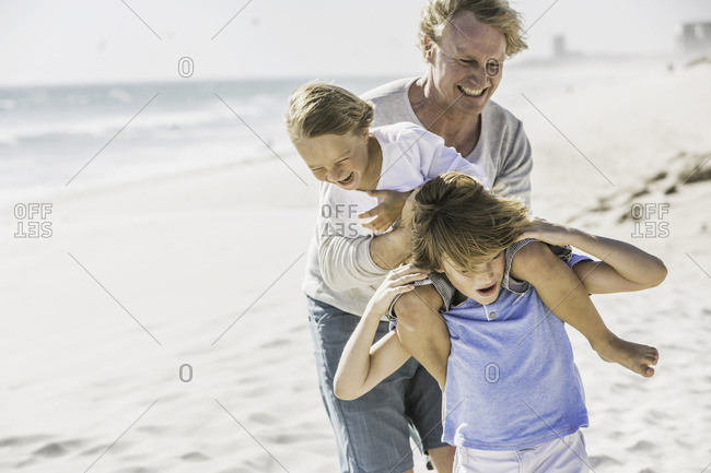 Father helping sons with piggyback on beach