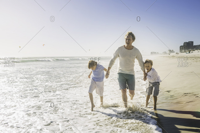 Father and sons holding hands on beach