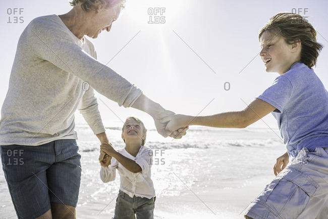 Father and sons playing on beach