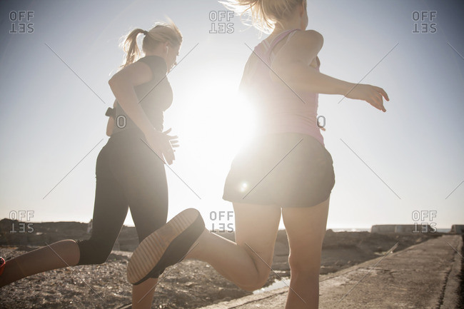 Two young female runners running along sunlit coast, Seapoint, Cape Town, South Africa
