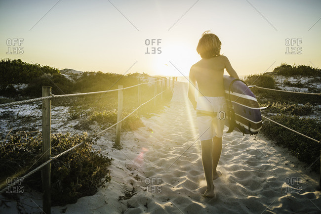 Young boy, walking along beach walkway, holding surfboard, rear view
