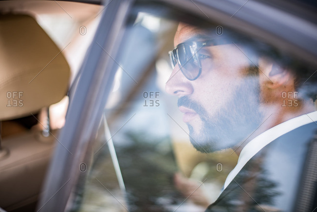 Young businessman wearing sunglasses looking out of car window from backseat, Dubai, United Arab Emirates