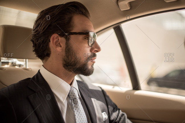 Young businessman looking out from car backseat, Dubai, United Arab Emirates