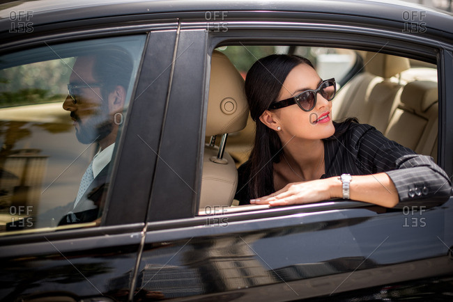 Stylish businesswoman looking back from backseat car window, Dubai, United Arab Emirates