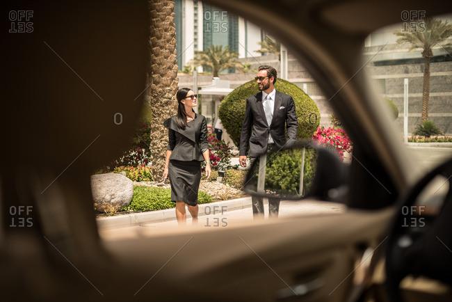 Car window view of businesswoman and man walking outside hotel, Dubai, United Arab Emirates